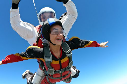 Living life Woman and Man skydiving in tandem